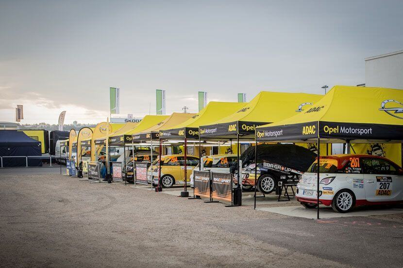 Race cars under tents at ADAC's race